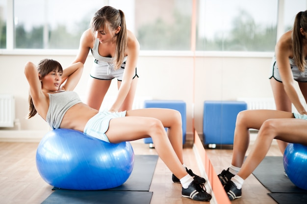 Young beautiful woman in sportswear helping another girl with using fitness ball in gym