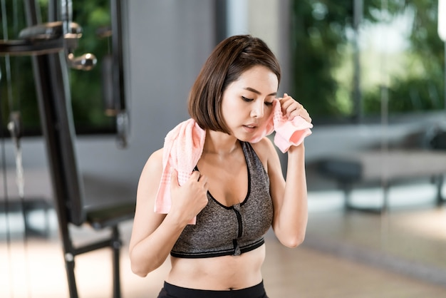 Young beautiful woman in sportswear working out in gym