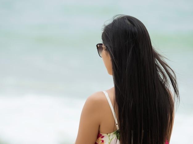 後ろに立って海の波を見ている若い美しい女性。自由、孤独、夏時間または休暇の概念
