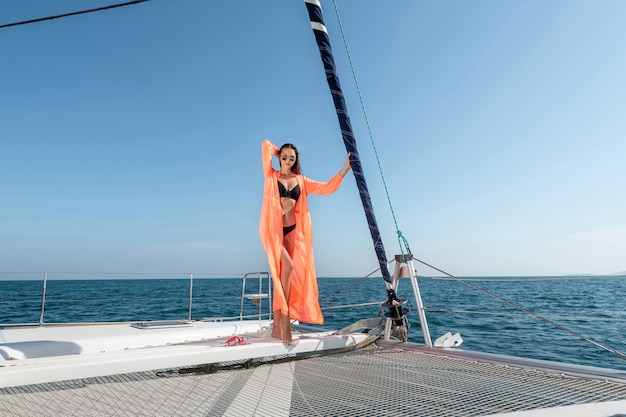 Young beautiful woman standing on the bow of the yacht