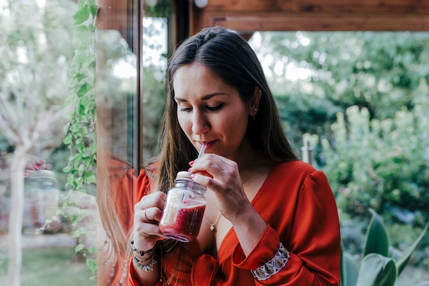 Young beautiful woman standing by the window holding a healthy jug of smoothie. home, indoors and lifestyle