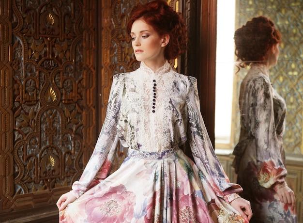 거울 궁전 방에 서있는 젊은 아름 다운 여자.