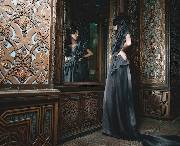 궁전 방에 서있는 젊은 아름 다운 여자