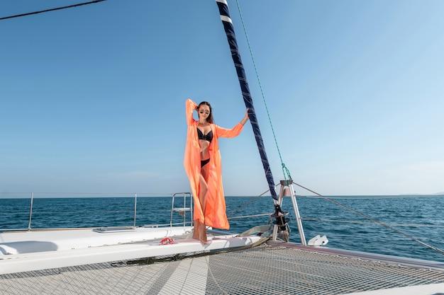 Молодая красивая женщина, стоящая на носу яхты