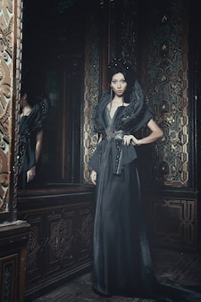 Young beautiful woman standing in the palace room