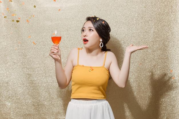 シャンパングラスを手に立って、金色のきらびやかな背景の上に紙吹雪をキャッチする若い美しい女性。