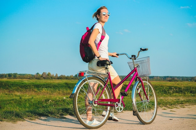 緑の野原の背景に夏のピンクの自転車のクローズアップで立っている若い美しい女性