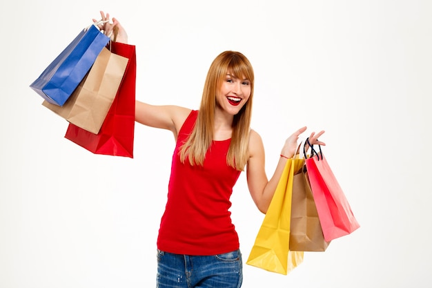 Young beautiful woman standing with purchases over white wall