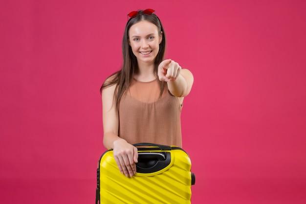 Giovane bella donna in piedi con la valigia di viaggio che punta il dito alla fotocamera sorridente con la faccia felice su sfondo rosa