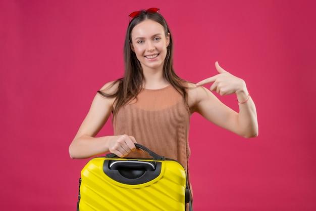 ピンクの背景の上の幸せそうな顔で笑って自分に旅行スーツケース人差し指で立っている若い美しい女性