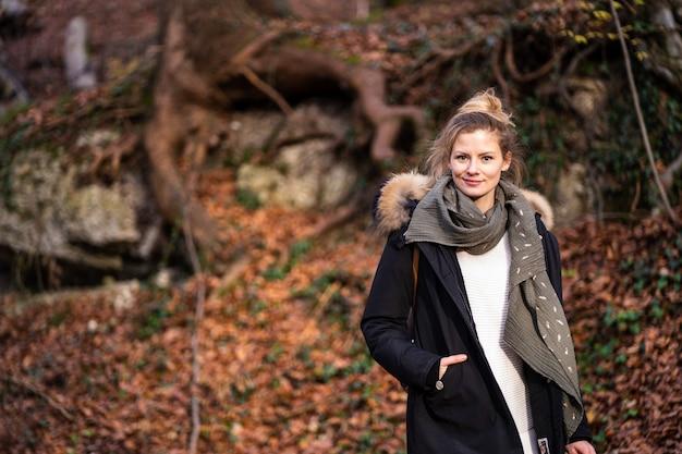 아름 다운 젊은 여자는 단풍 숲에 서있다. 겨울 옷은 추위로부터 보호합니다.