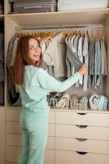 Молодая красивая женщина стоит возле шкафа и вешает одежду. футболки сложены вертикально в белую корзину. хранение одежды.