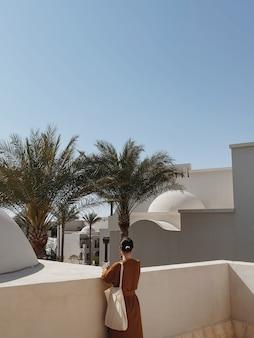 젊은 아름다운 여자는 베이지 색 벽, 열대 야자수가있는 현대 동쪽 스타일 건물의 지붕에 머물러 있습니다.