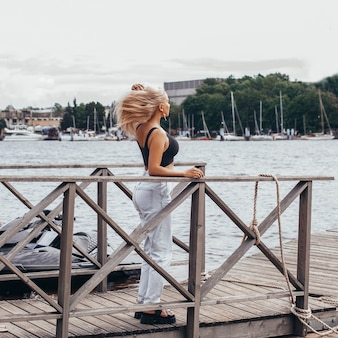 Young beautiful woman staying on the wooden pier and looking at the sea