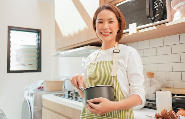 Young beautiful woman stirring ingredients in a pot