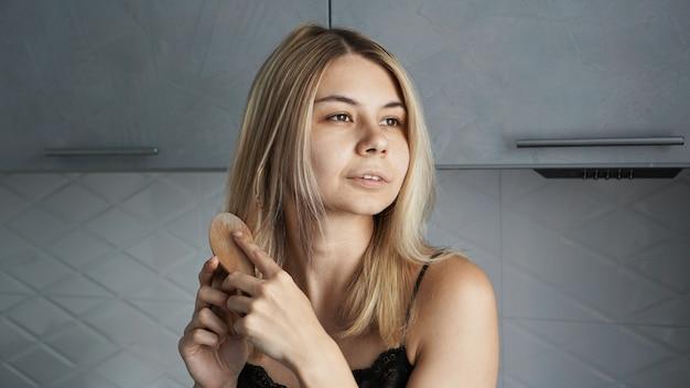 自宅で彼女のブロンドの髪をまっすぐにする若い美しい女性