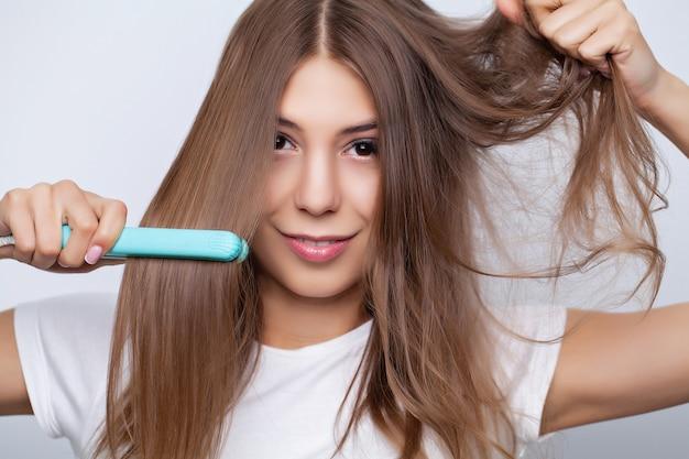 Молодая красивая женщина поправляет волосы в гостиной.