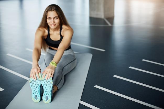 トレーニング前にストレッチする若い美しい女性。スニーカーの靴底に焦点を当てます。