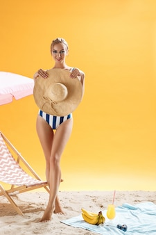Young beautiful woman in striped bath suit holding straw hat