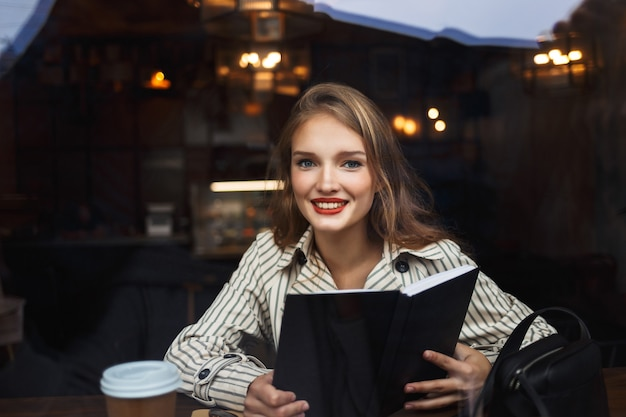 Young beautiful woman in striped trench coat holding book in hands happily