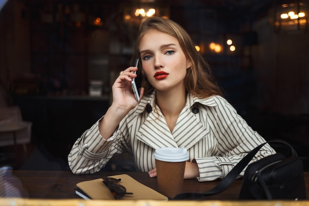 Young beautiful woman in striped trench coat talking on cellphone thoughtfully
