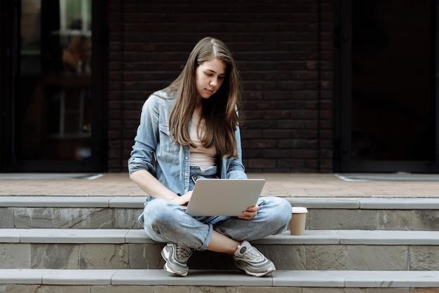 젊은 아름다운 여자 학생 또는 노트북을 사용하는 프리랜서