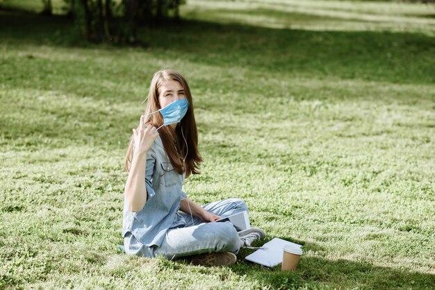 아름 다운 젊은 여자 학생 또는 헤드폰 프리랜서 의료 마스크를 벗고 태블릿에서 배운다
