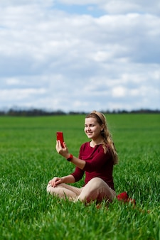 草の上に座っている彼女の手に携帯電話を持つ若い美しい女性の学生。女の子は自分撮りを撮り、自分撮り写真を撮ります。彼女は微笑んで暖かい日を楽しんでいます。スマートフォンのコンセプト写真