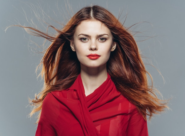 Young beautiful woman in studio, red color