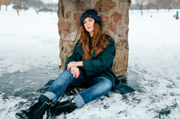 Young beautiful  woman in stylish clothes with long brown hair sitting under bridge on ice on frozen lake in cold frost winter day