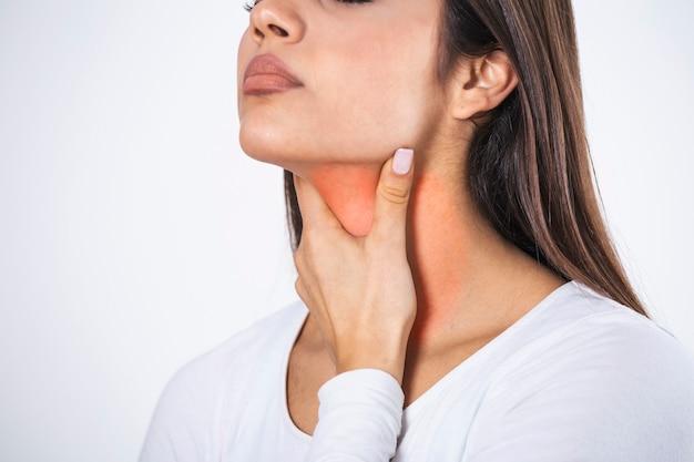 Молодая красивая женщина страдает от боли в горле, касаясь воспаленной зоны на шее