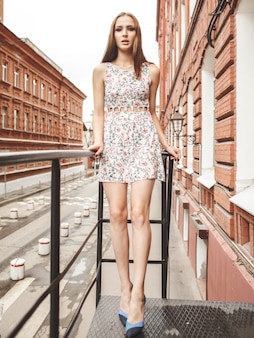 Young beautiful woman in summer dress on street on city