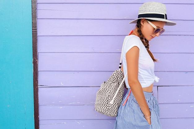 Giovane bella donna in abito di moda estiva, stile casual, in posa contro il muro colorato, viaggiare, cappello, occhiali da sole, sorridente, felice