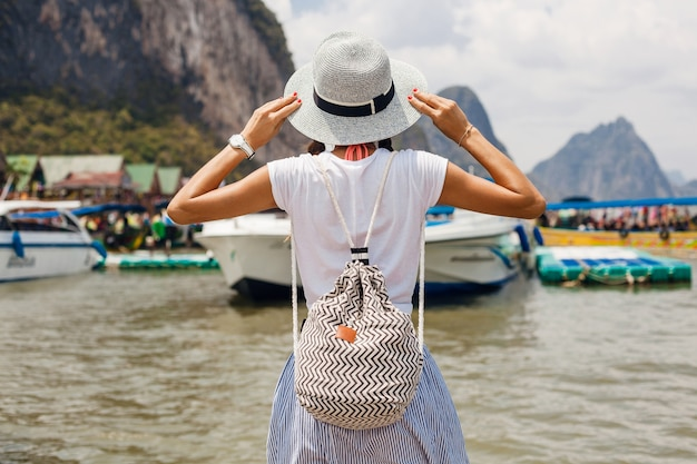 Young beautiful woman in summer fashion outfit, casual style, traveling with backpack, hat, sunglasses, vacation in thailand, asia