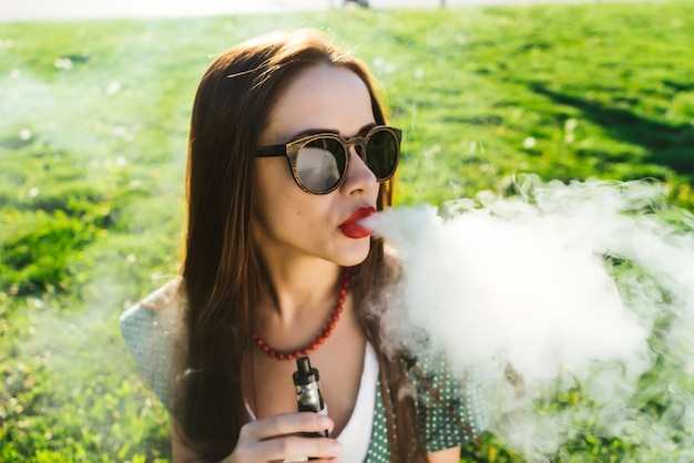 Young beautiful woman in sunglasses is sitting on the lawn with bright green grass, smoking, looking to the right. sunny day