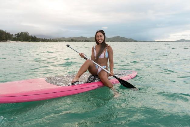 Young beautiful woman surfing in hawaii