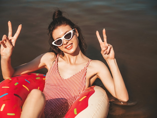 Young beautiful woman in swimwear and sunglasses floating on the sea