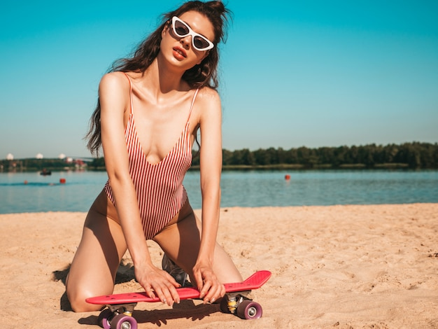 Young beautiful woman in swimwear and sunglasses posing at the beach