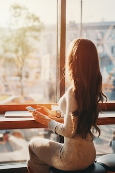 Young beautiful woman at a table in cafe looks at city through the window