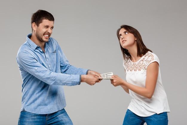 灰色の壁を越えて男からお金を取る若い美しい女性