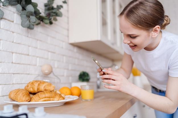 Молодая красивая женщина, делающая фото на мобильный телефон круассанов