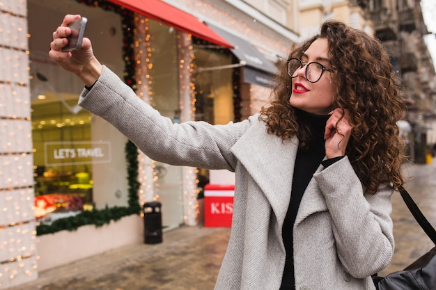 Young beautiful woman taking seflie picture using smartphone, autumn street city style, warm coat, glasses, happy, smiling, holding phone in hand, curly hair