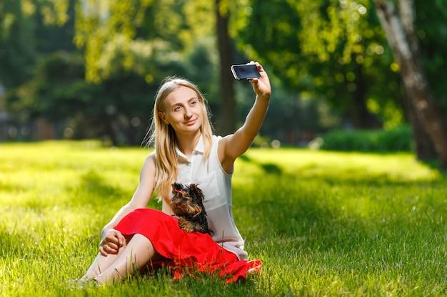 Молодая красивая женщина, принимая селфи со своей собакой