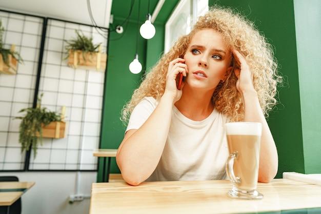 Молодая красивая женщина разговаривает по телефону в кафе