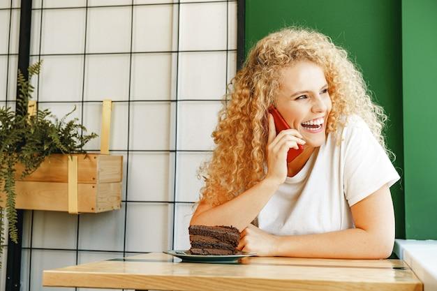 Молодая красивая женщина разговаривает по телефону в кафетерии крупным планом