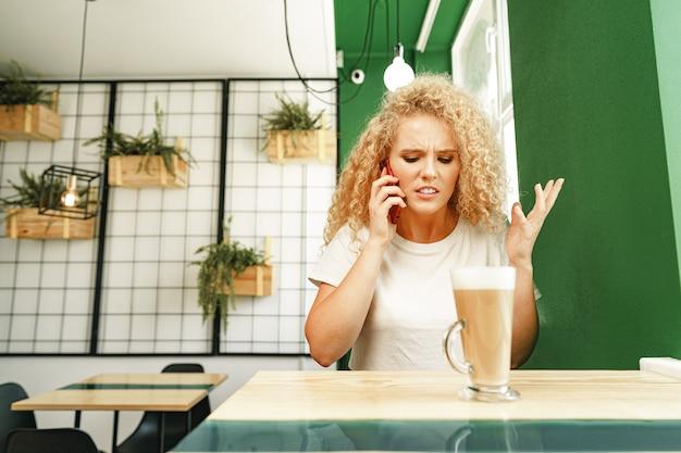 Молодая красивая женщина разговаривает по телефону в кафетерии