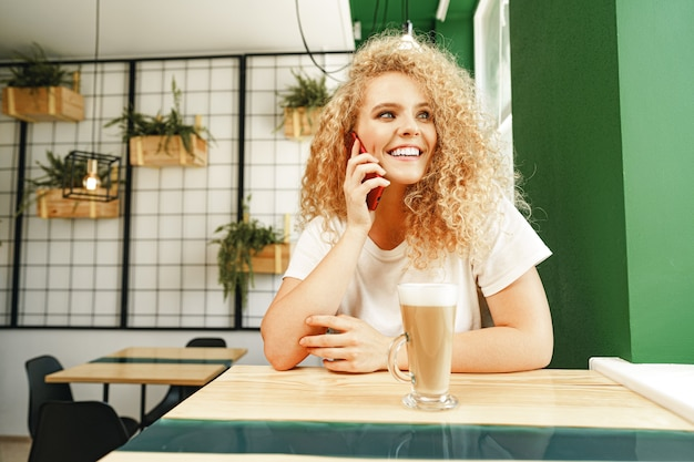 Young beautiful woman talking on the phone in cafeteria close up