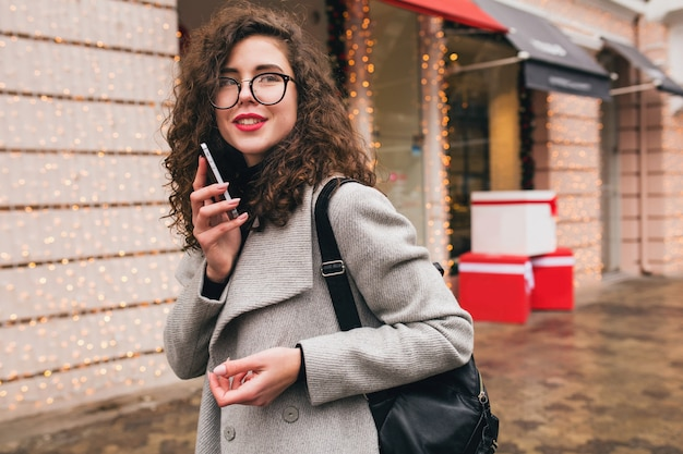 Young beautiful woman talking on smartphone, autumn street city style, warm coat, glasses, happy, smiling, holding phone in hand, curly hair