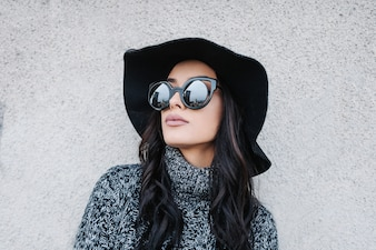 Young beautiful woman tanding in front a wall wearing trendy fall outfit.