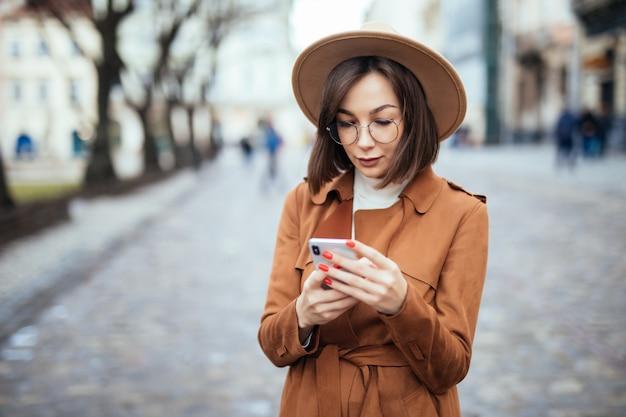 スマートフォン秋のストリートで若い美しい女性のテキストメッセージ